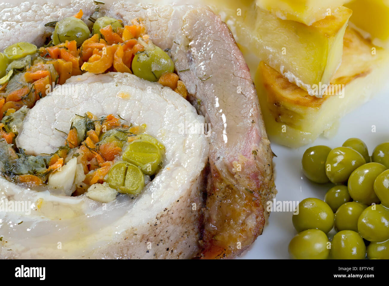 Close-up view of home meatloaf with roasted potatoes and green peas. Stock Photo