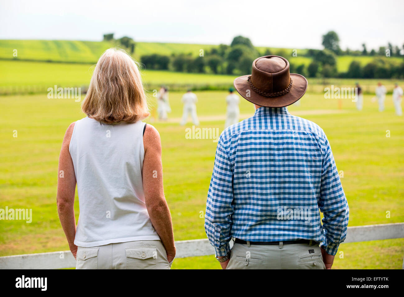 Rear view of couple watching cricket match on cricket field Stock Photo