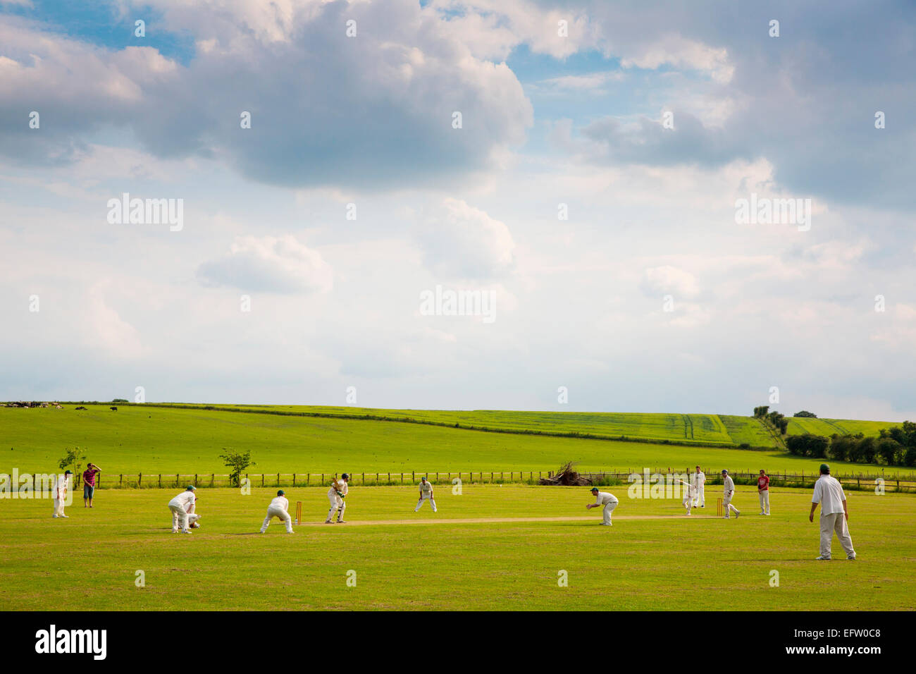 Rural scene with view cricket players playing cricket match on cricket field Stock Photo