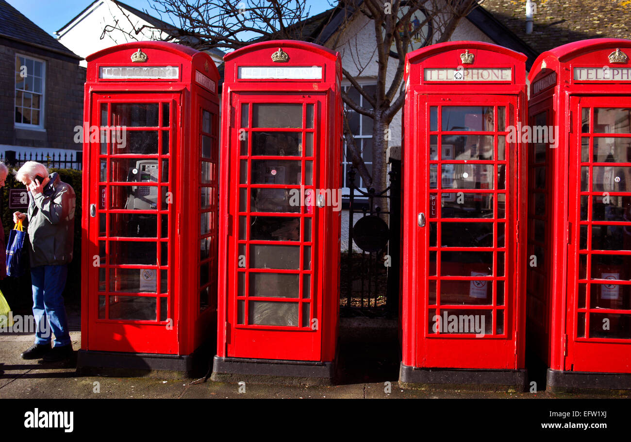 A pedestrian using a mobile phone next to traditional red telephone call boxes in Truro, Cornwall. - Stock Image