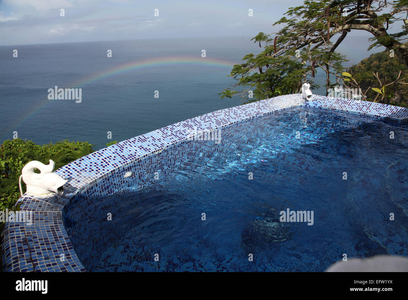 A Plunge pool and Carob Tree on the edge of the Caribbean ocean with a rainbow behind - Stock Image