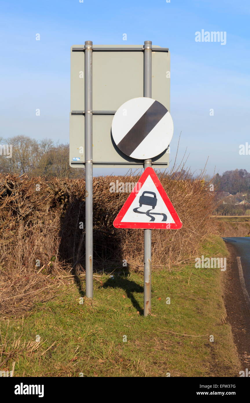 National speed limit applies and slippery road caution sign - Stock Image