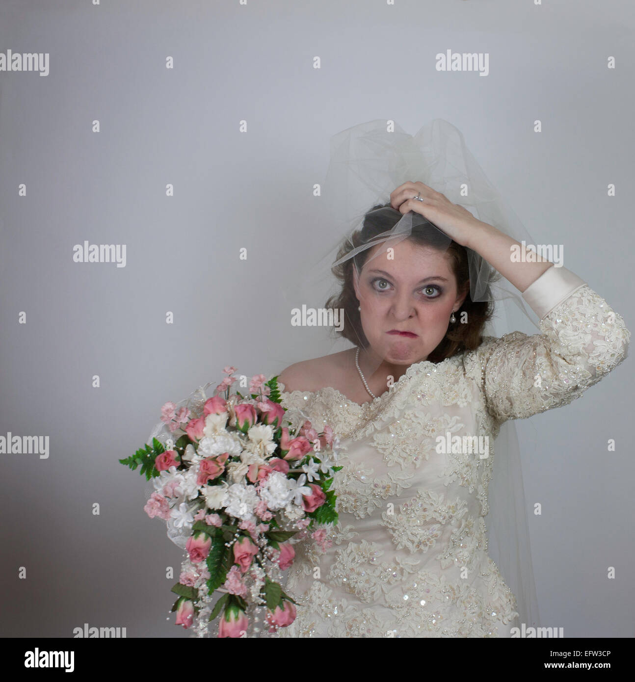 Young bride makes a stressful face and holds bouquet as she grips her veil in her hand. - Stock Image
