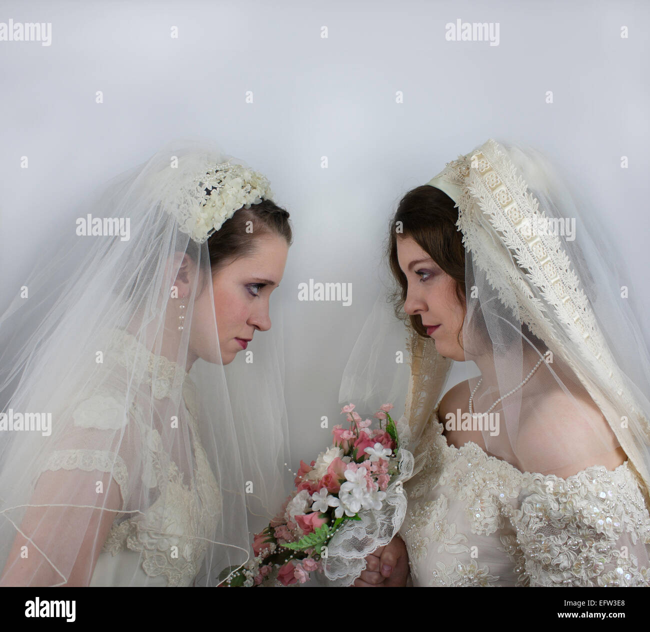 Two young brides staring at each other like bridezillas - Stock Image