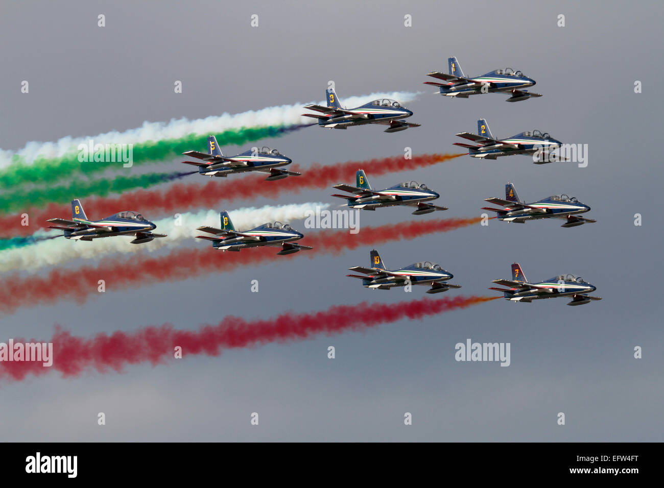 Italy's Frecce Tricolori aerobatic display team flying in formation and making smoke during an airshow display - Stock Image