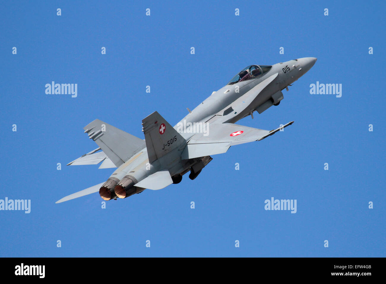 Swiss Air Force F-18 Hornet fighter jet aircraft taking off against a clear blue sky. Military aviation. - Stock Image