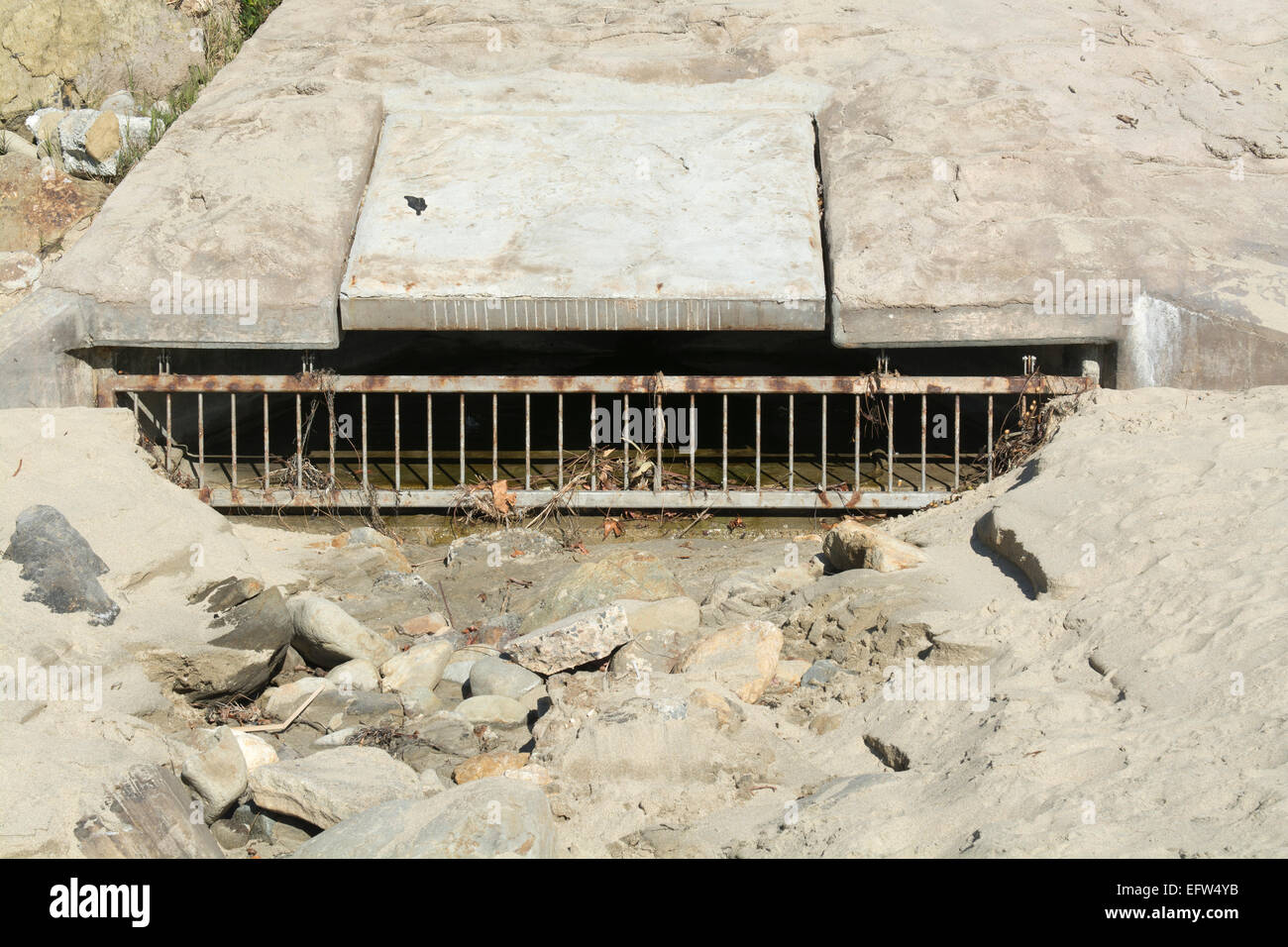 A beach sewer used to drain water runoff from the cliff side during heavy rains to control flooding - Stock Image