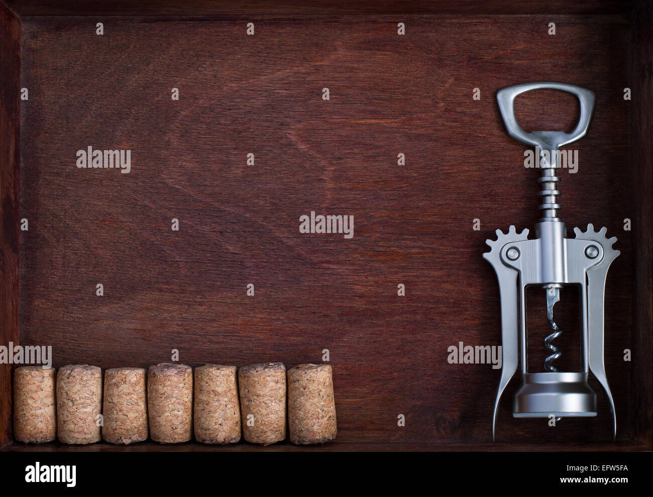 Corkscrew and a row of identical wine corks into dark box - Stock Image