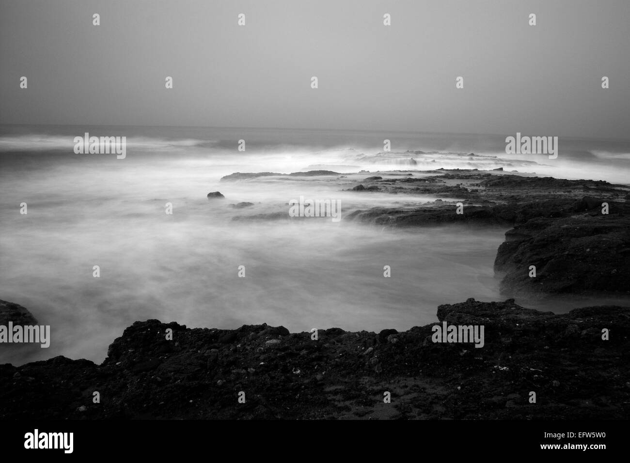 An early morning slow motion images of seawater rushing over sharp, rugged shoreline reef in Laguna Beach, California. - Stock Image