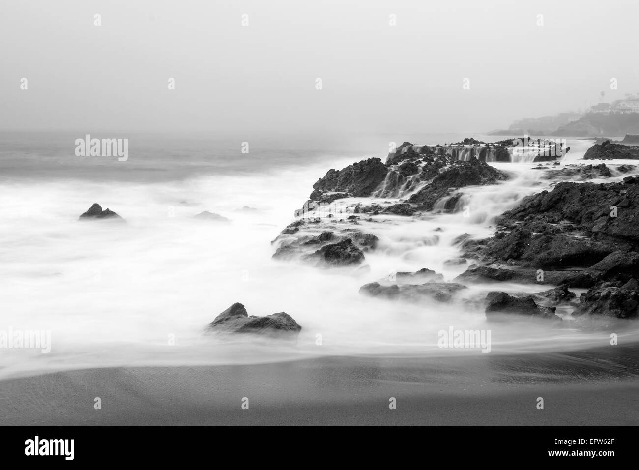 An early morning slow motion images of seawater rushing over sharp, rugged shoreline reef in Laguna Beach, California. Stock Photo