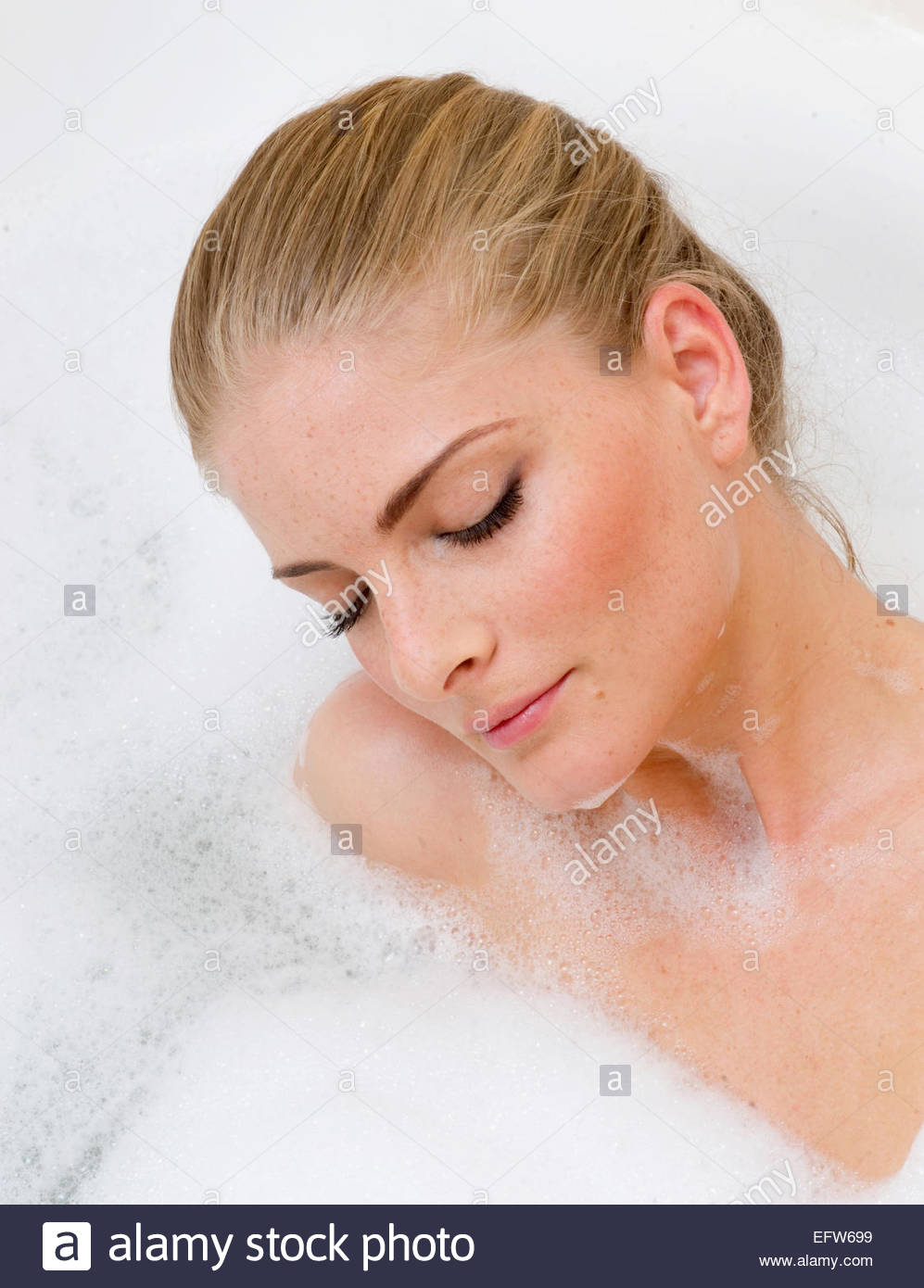 Young washing bathtub bathroom bath bathing Woman Bathtub Shampoo Washing Hair Lifestyle Portrait Young Adult One - Stock Image