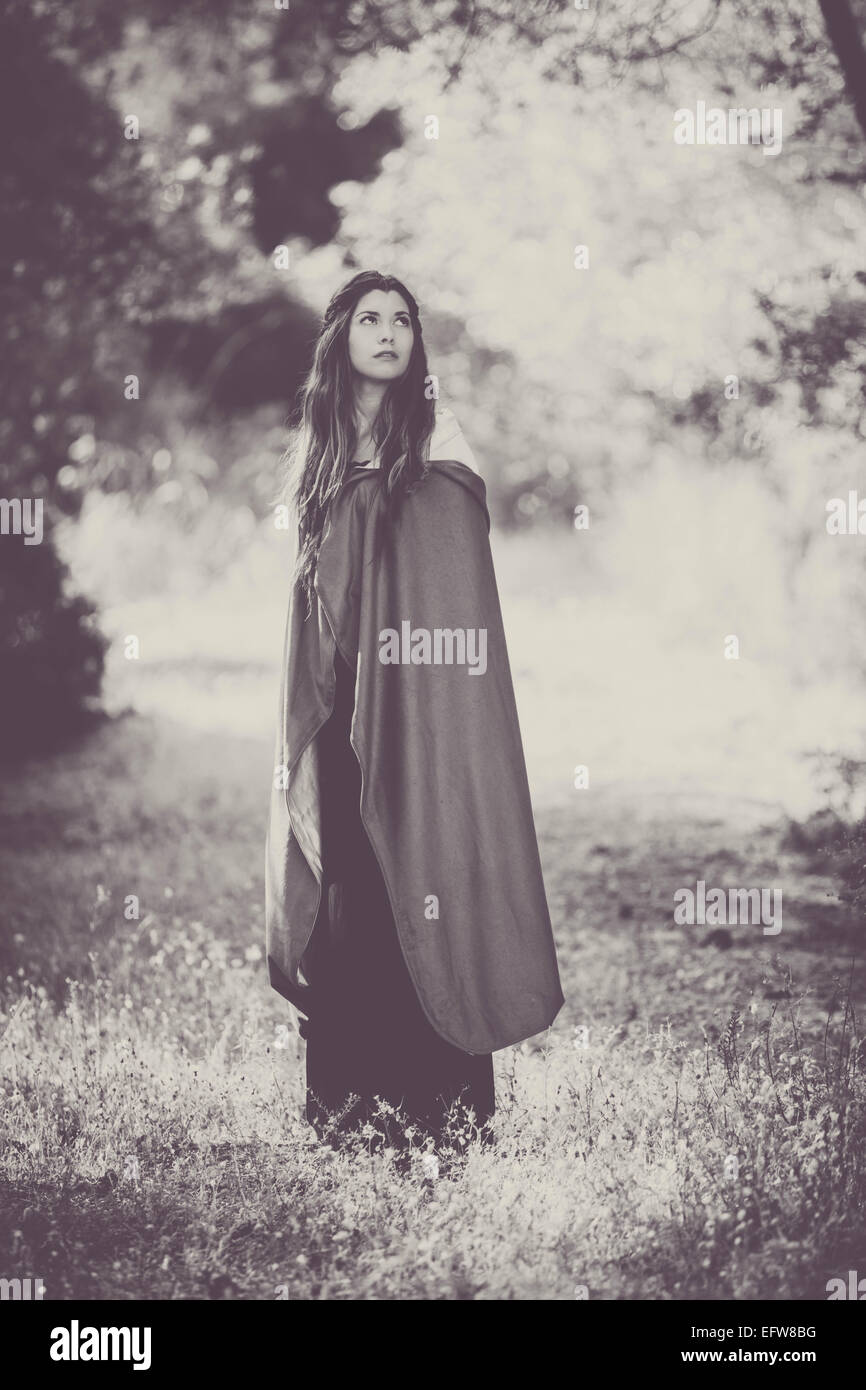 fiction woman in cloak in forest. - Stock Image