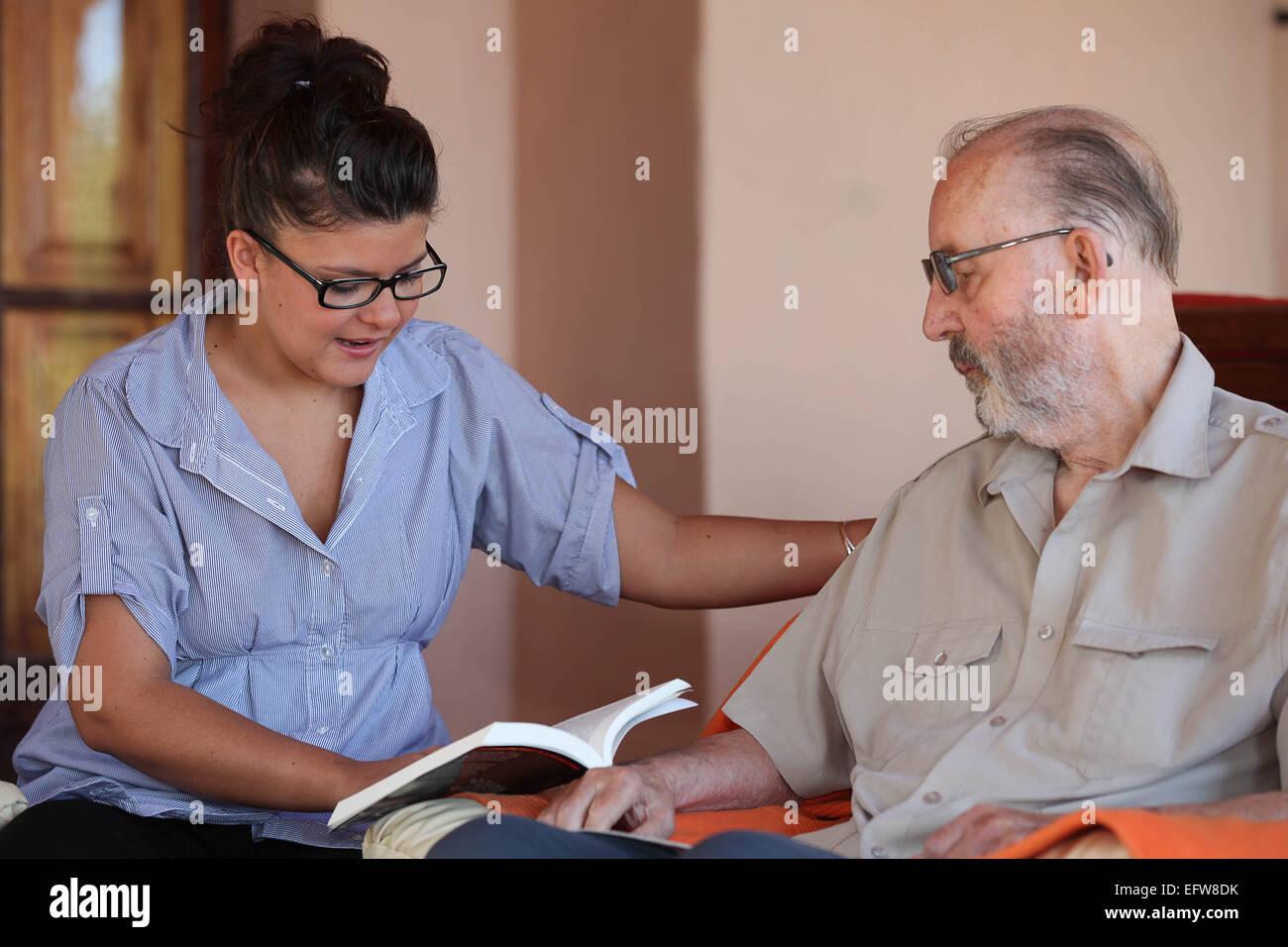 companion or grandchild reading to elderly senior or grandfather - Stock Image