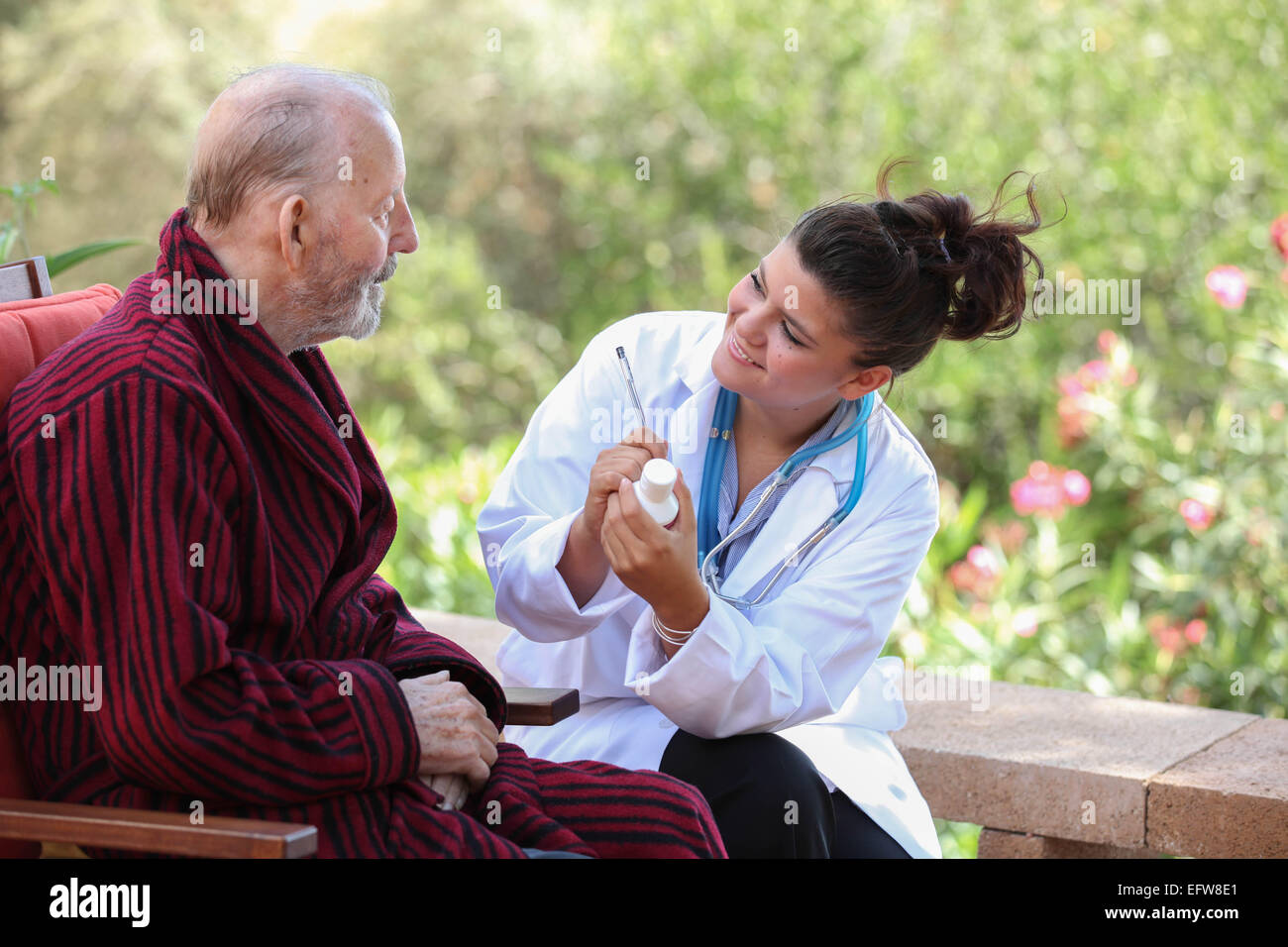 smiling Dr or nurse giving medication to senior patient. - Stock Image