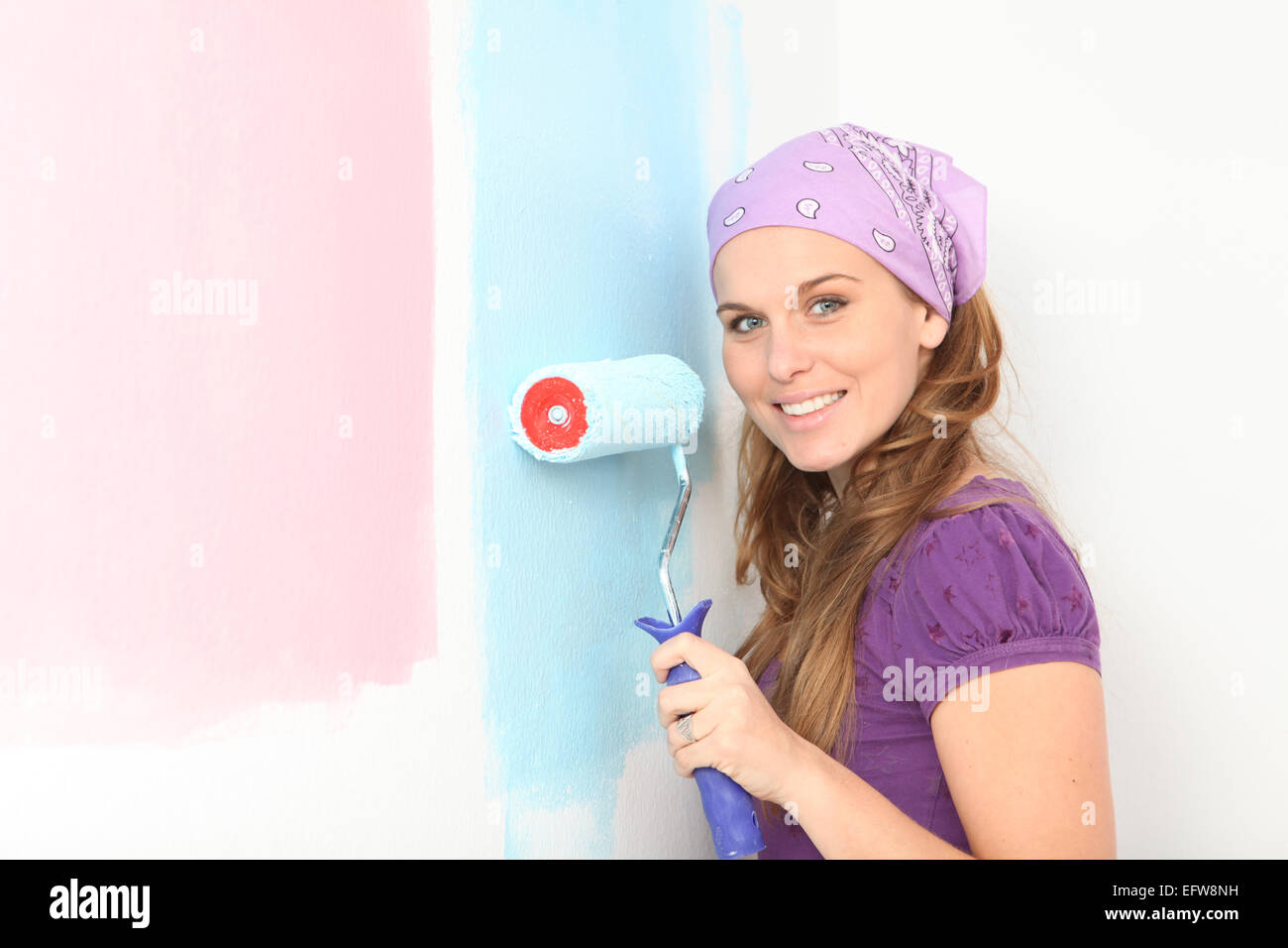 early pregnant woman deciding to paint nursery pink or blue. - Stock Image