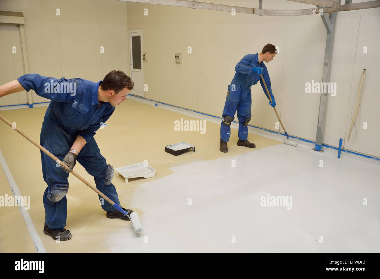 Two tradesmen roll a second coat of tinted epoxy product on the floor of an industrial building - Stock Image
