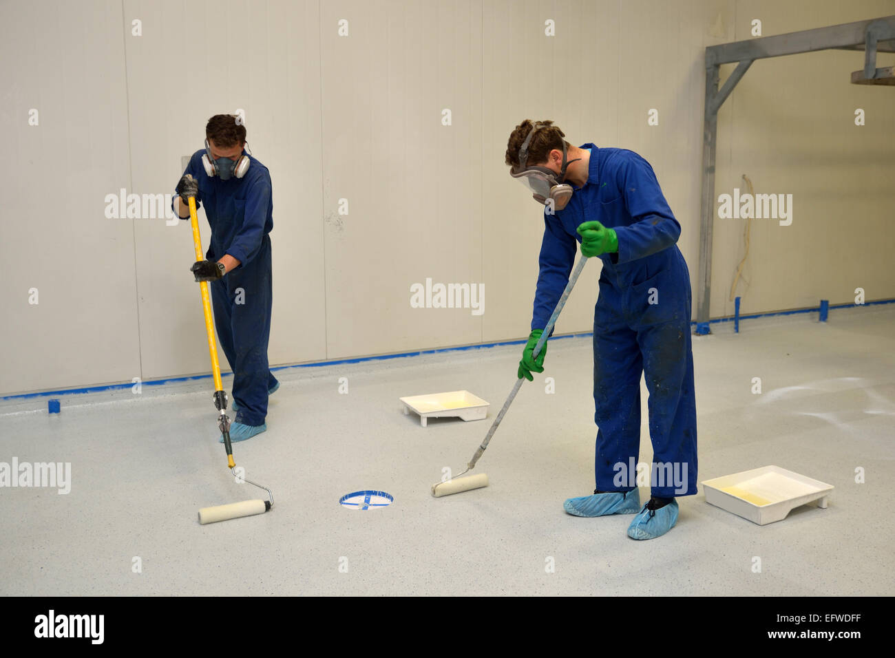 tradesmen roll a final coat of clear epoxy product on the floor of an industrial building - Stock Image
