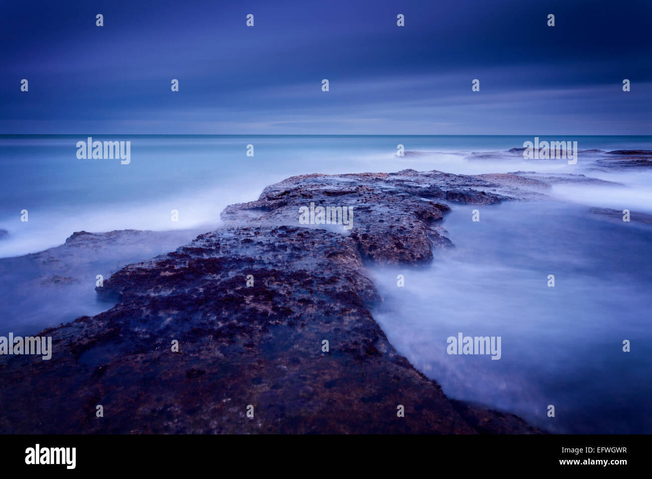 Large waves pounding the reef at Thorntonloch during the blue hour before sunrise. - Stock Image