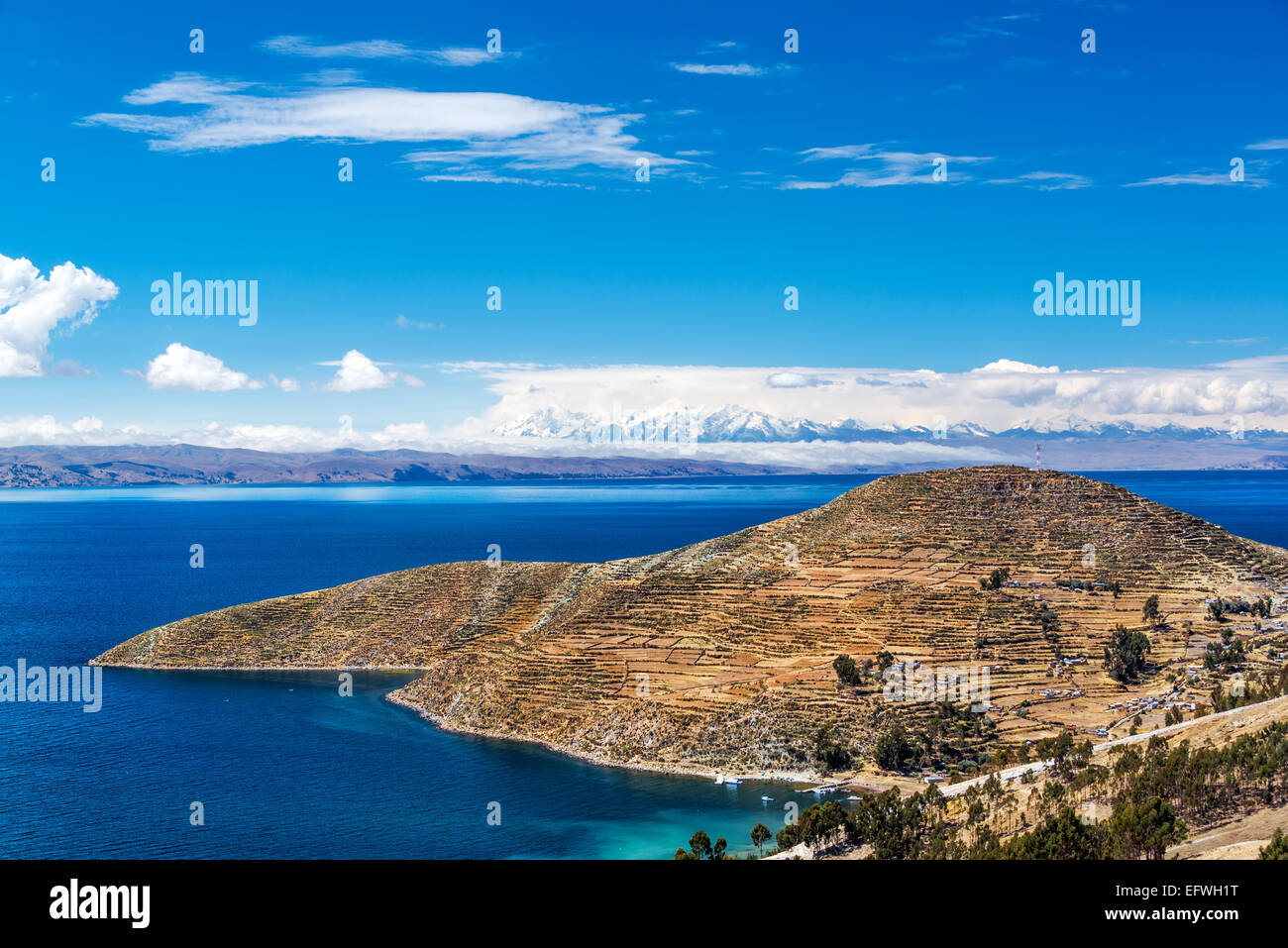 Terraced landscape of Isla del Sol with Andes mountains in the background on the Bolivian side of Lake Titicaca - Stock Image