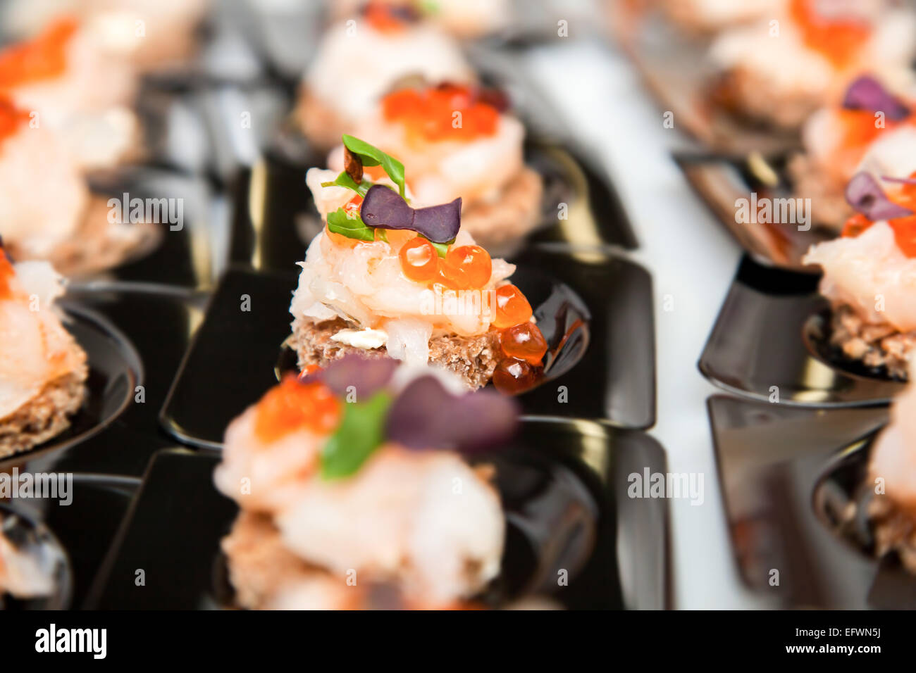Appetizer of Salmon eggs, fish, and green herbs canapés - Stock Image
