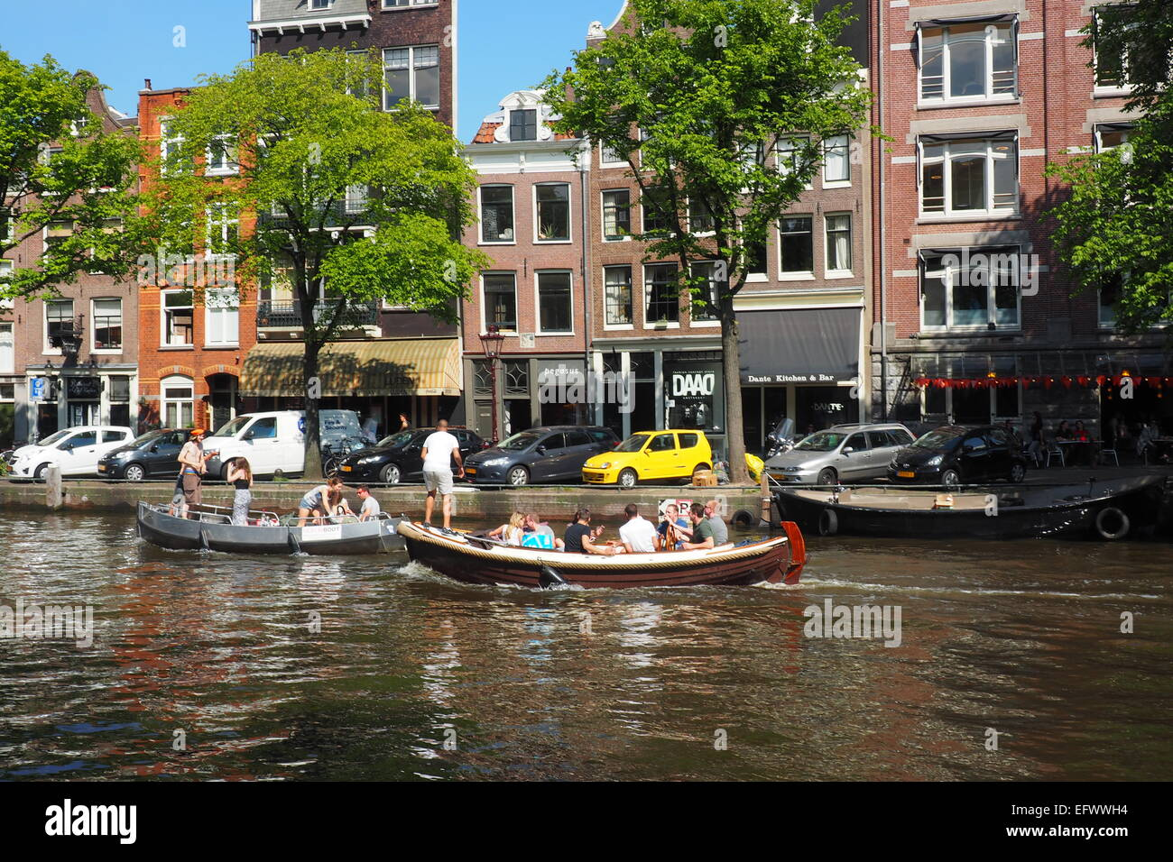 Young adults partying on two boats in an Amsterdam canal. - Stock Image