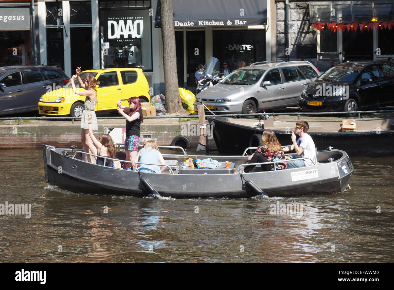 Young adults partying on a boat in an Amsterdam canal. - Stock Image