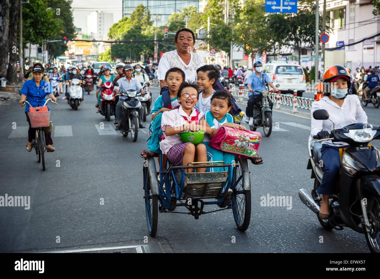 School kids riding a cyclo on a busy street, Ho Chi Minh City (Saigon), Vietnam. - Stock Image