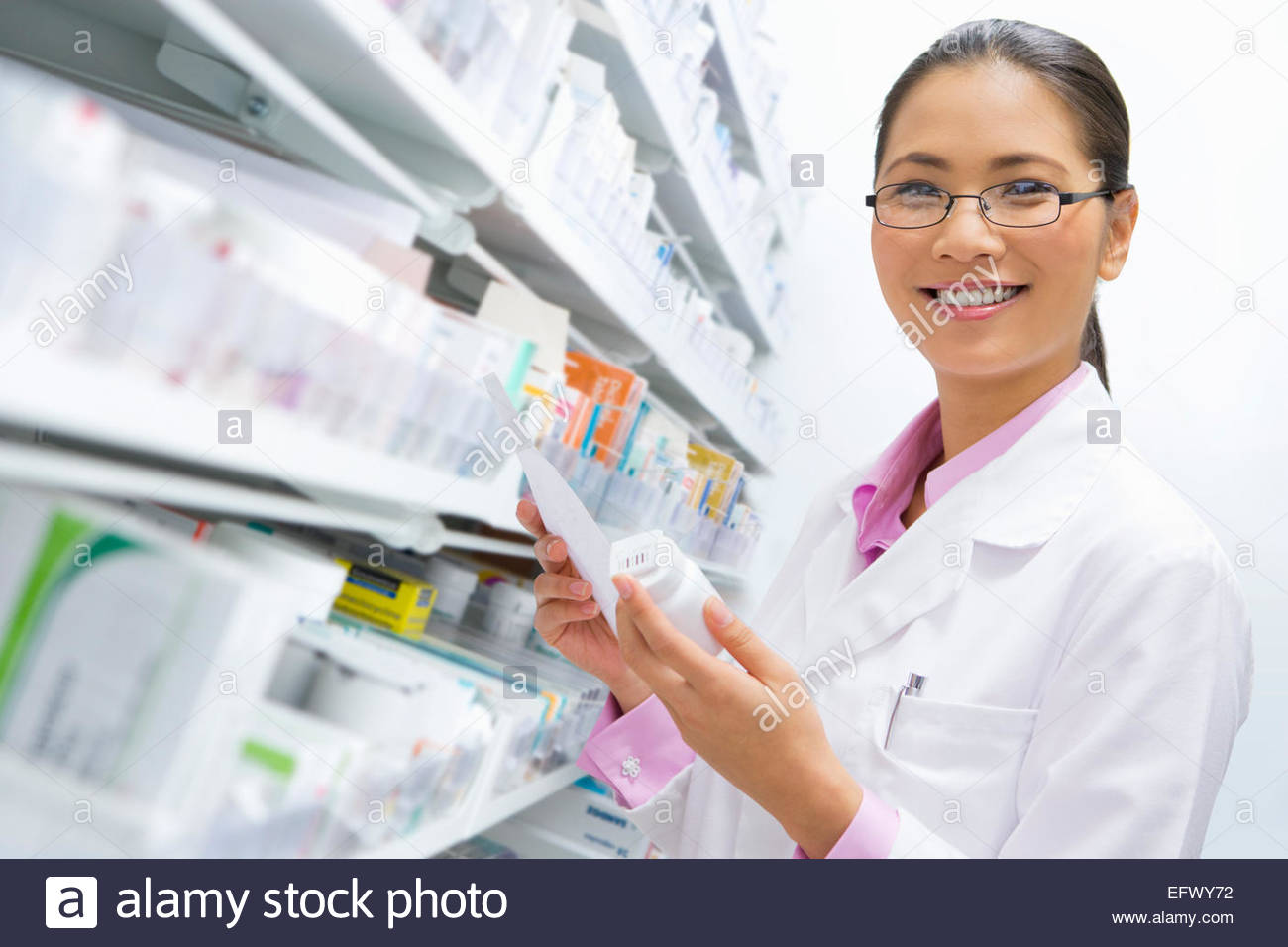 Pharmacist smiling at the camera holding pack of medication and prescription - Stock Image