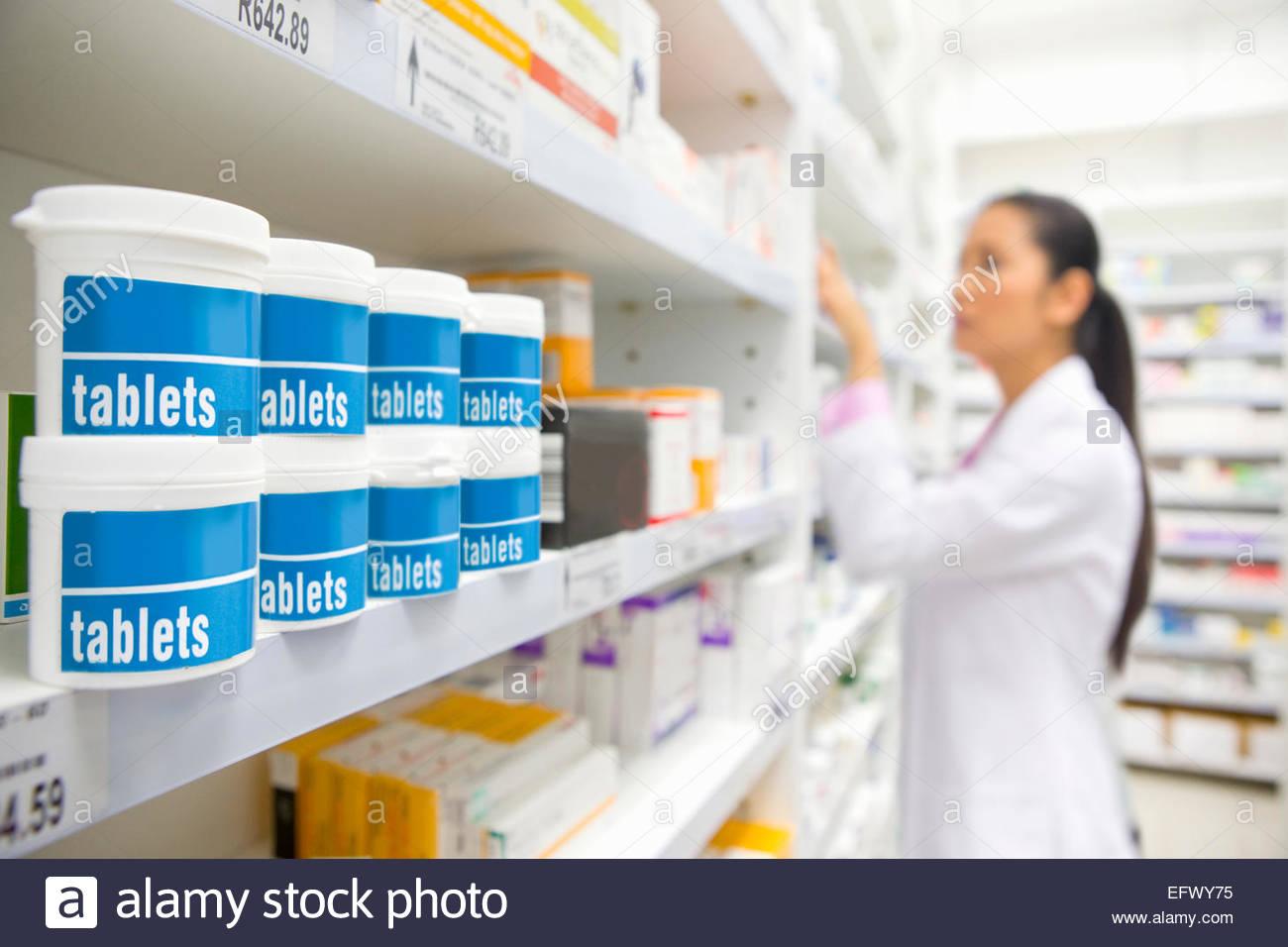 Pharmacist looking for medication on pharmacy shelf - Stock Image