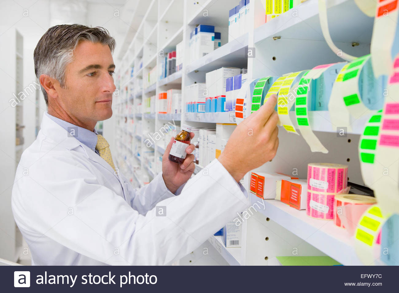 Pharmacist holding medication pot looking at labels on pharmacy shelf - Stock Image