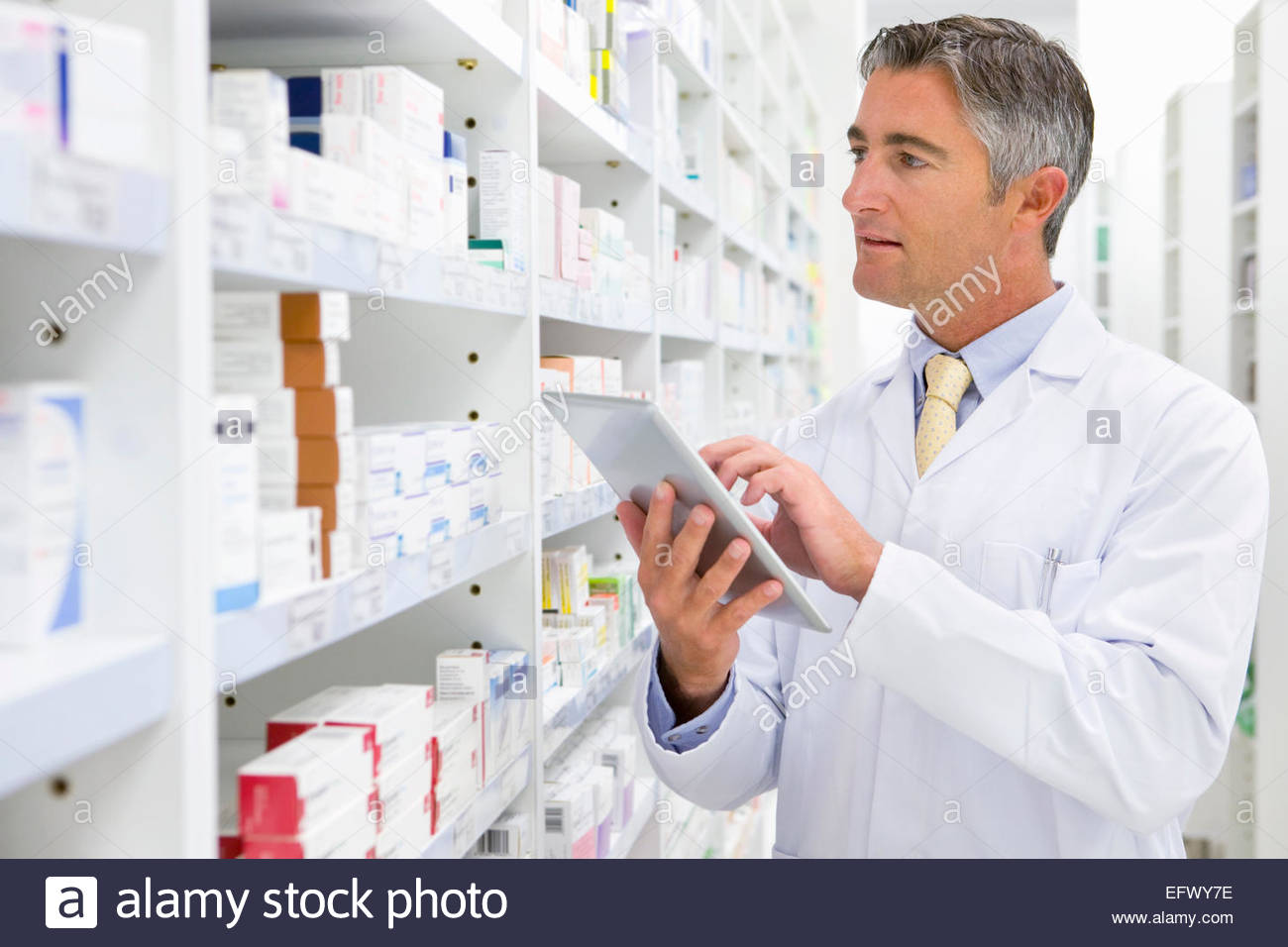 Pharmacist with digital tablet looking for medication on pharmacy shelf - Stock Image
