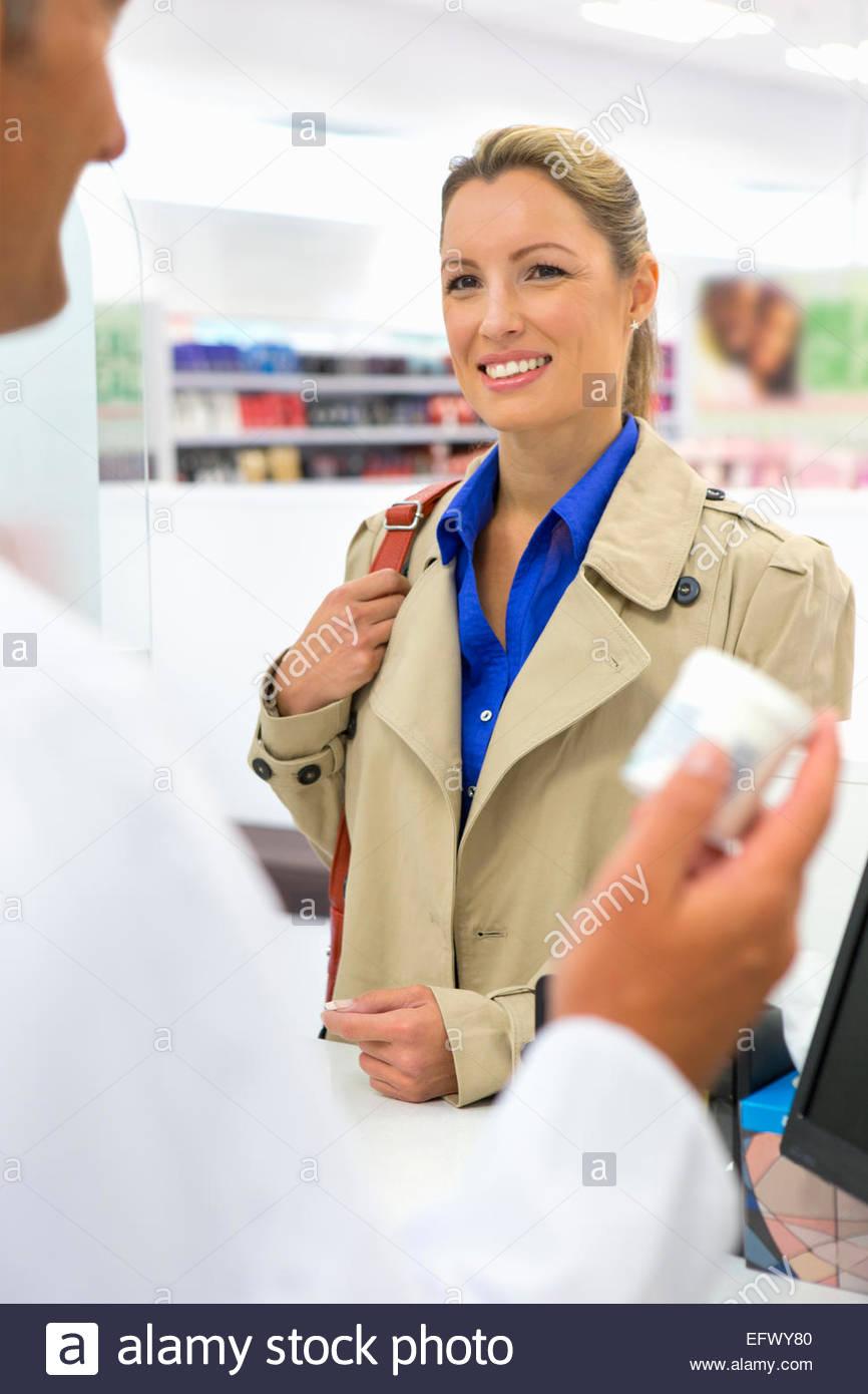 Smiling Female customer purchasing medication from pharmacist - Stock Image