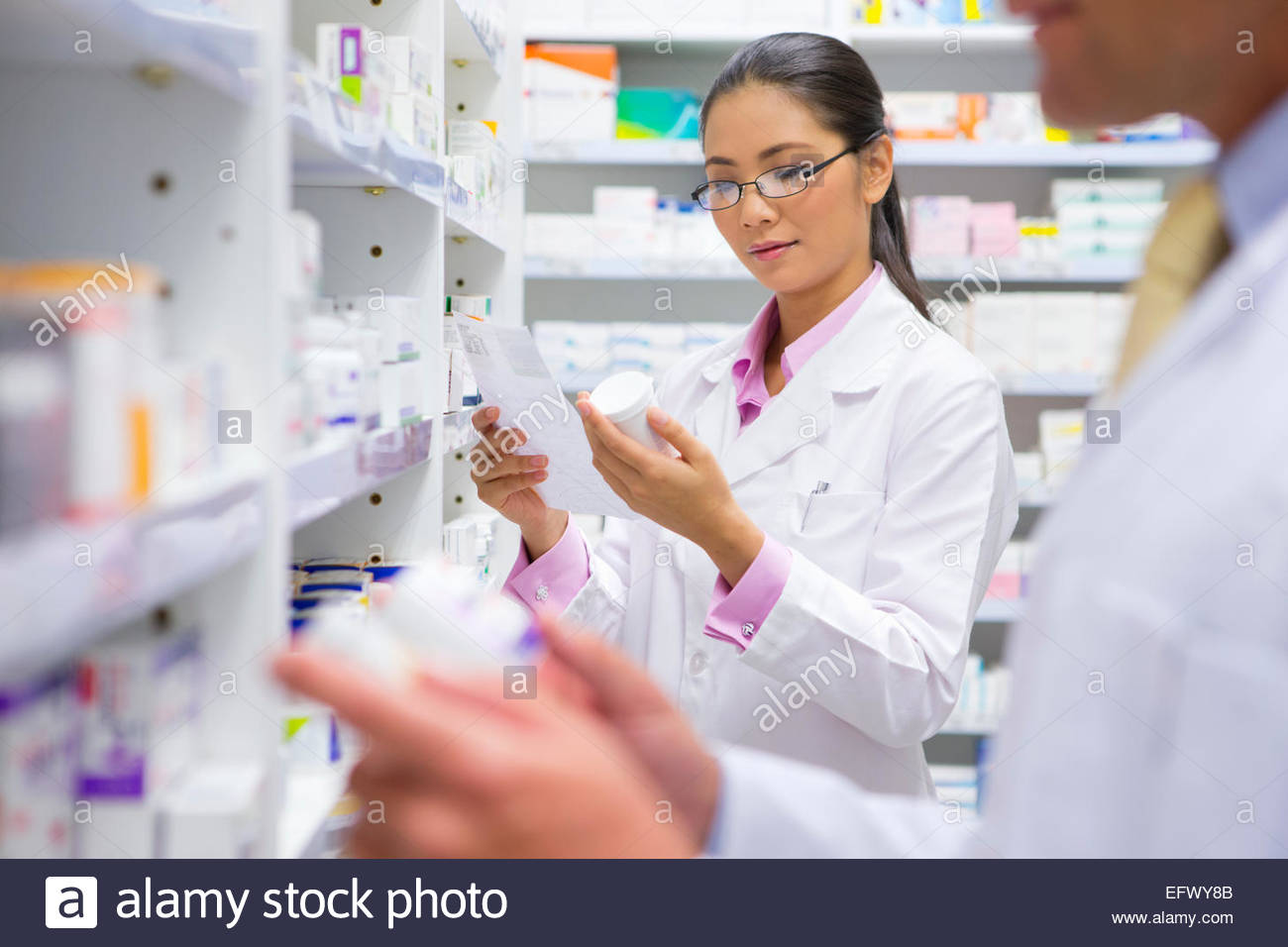 Pharmacists reading pack of medicine and prescription from pharmacy shelf - Stock Image