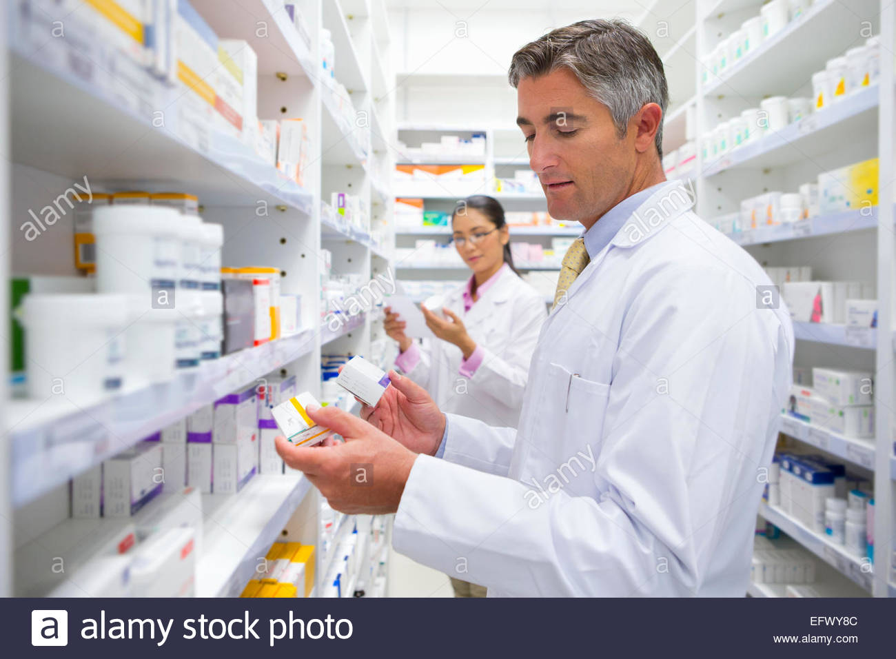 Pharmacists reading pack of medicine from pharmacy shelf - Stock Image