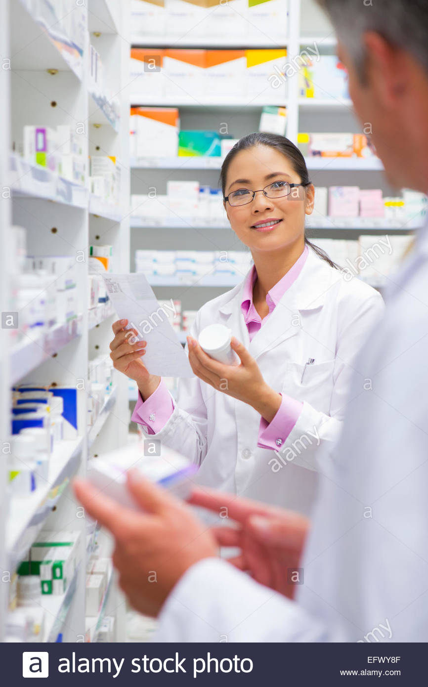 Pharmacist holding medication pack and prescription, talking to colleague in pharmacy - Stock Image