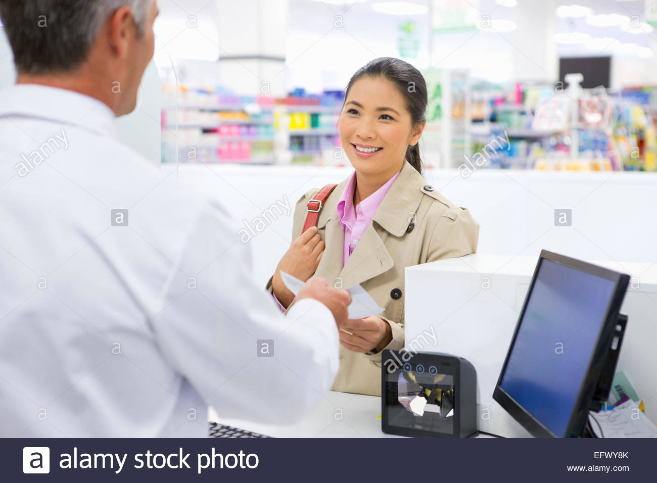 Female customer smiling and making a purchase in pharmacy - Stock Image
