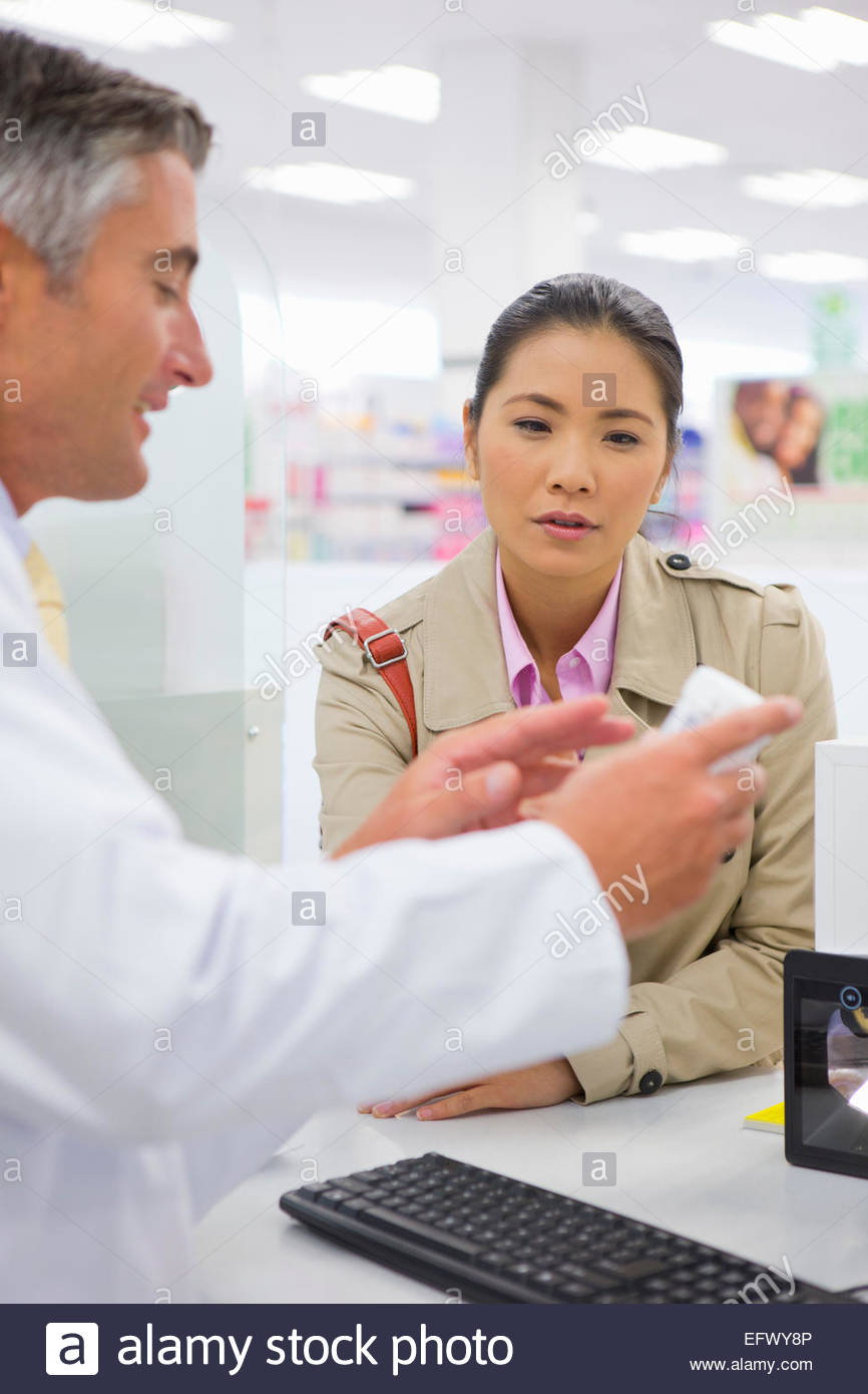 Pharmacist showing customer medication from behind pharmacy counter - Stock Image