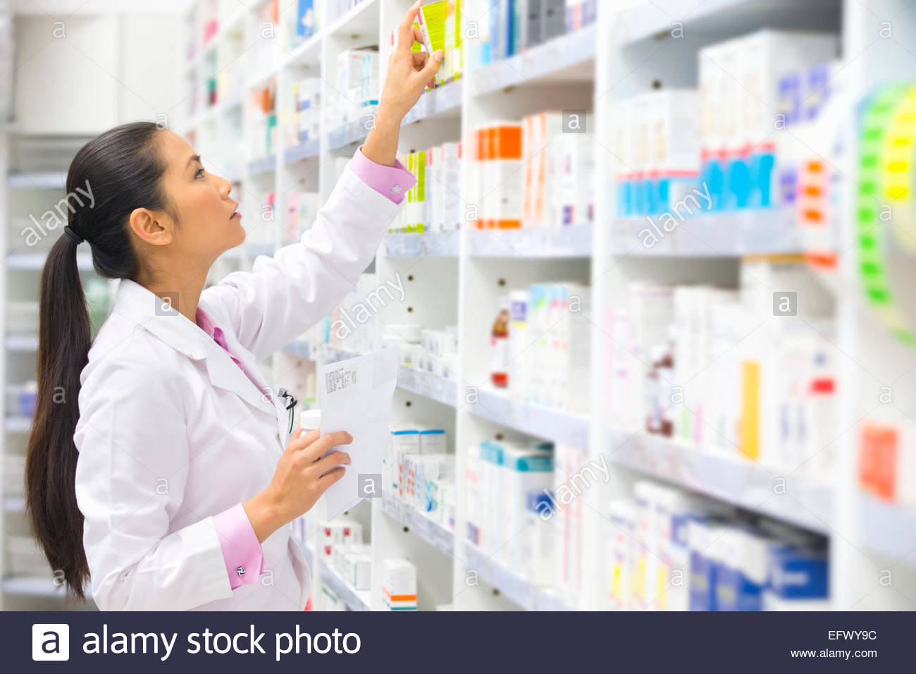 Pharmacist, holding prescription, looking for medication on pharmacy shelf - Stock Image