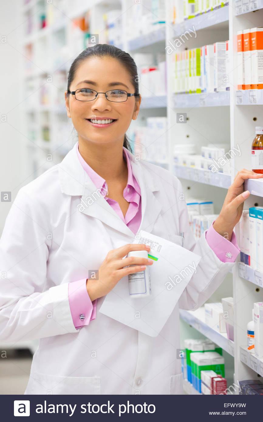 Pharmacist, holding prescription, smiling at camera standing next to pharmacy shelf - Stock Image