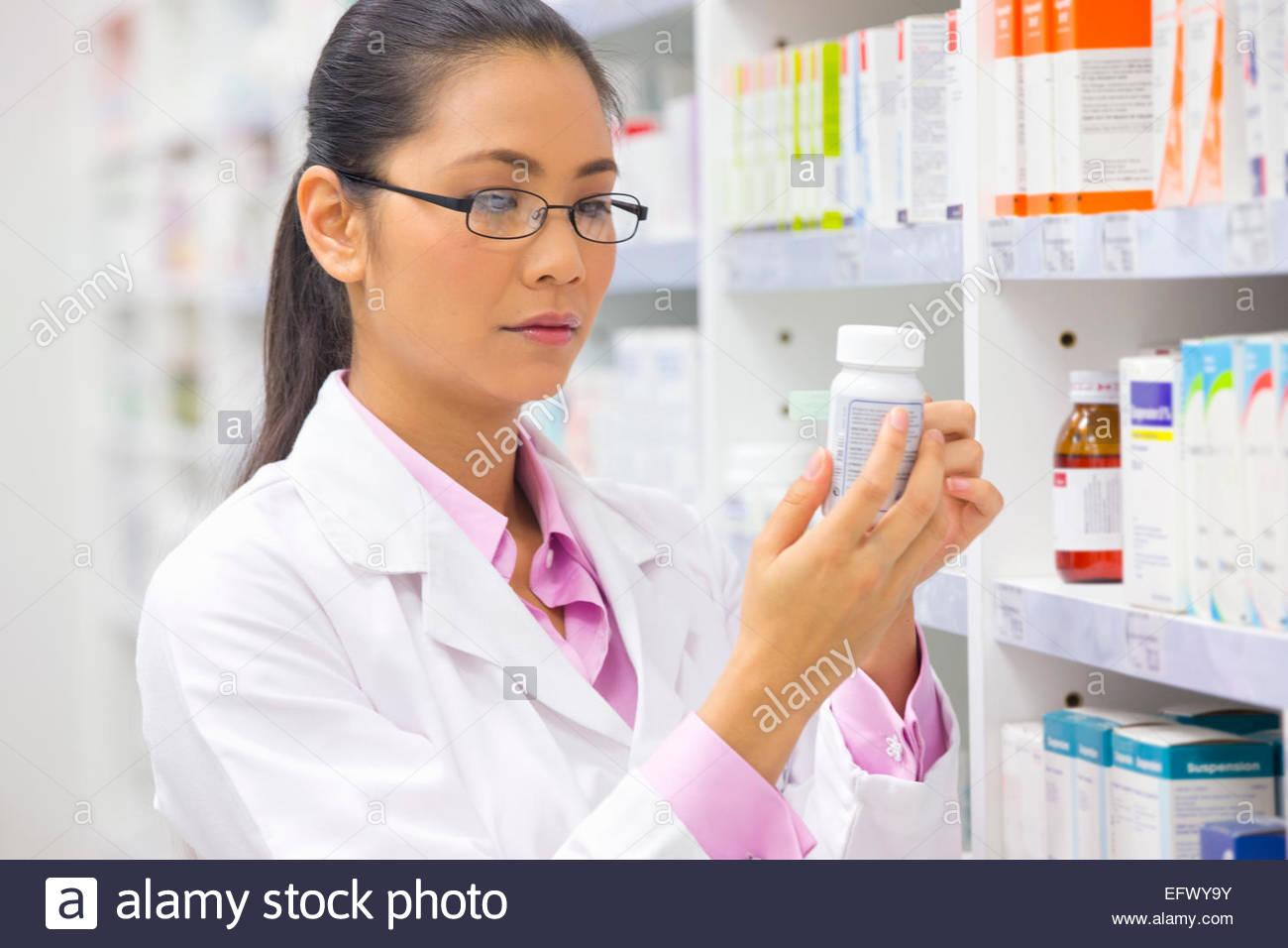 Pharmacist, reading medication pot from pharmacy shelf - Stock Image