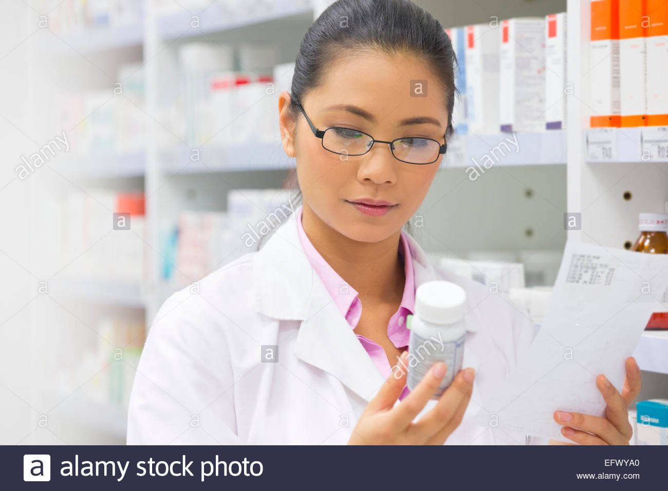 Pharmacist reading prescription and medication pot from pharmacy shelf - Stock Image