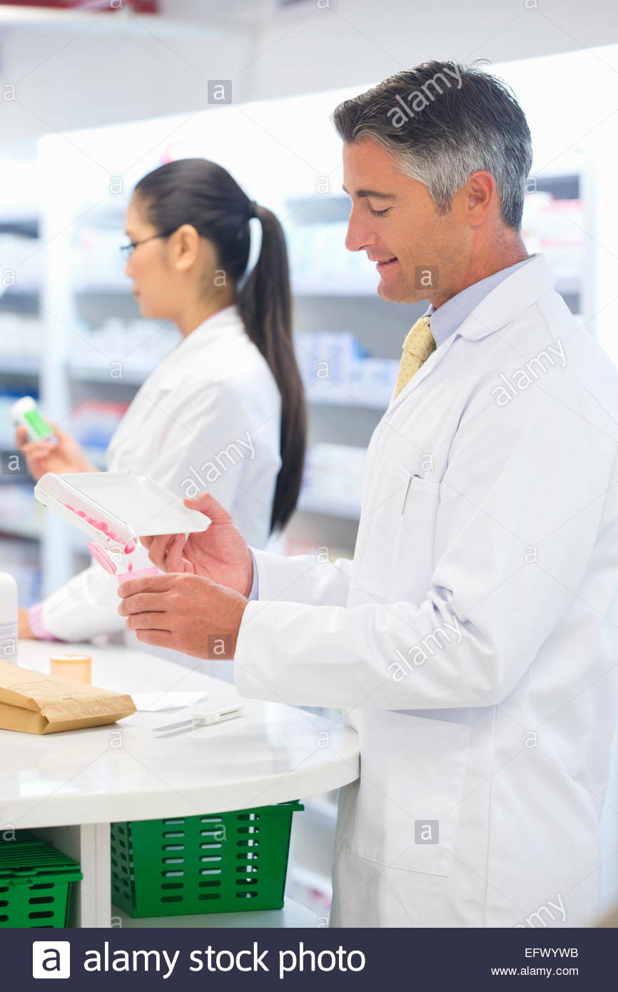 Pharmacist counting and dispensing medication behind pharmacy counter - Stock Image