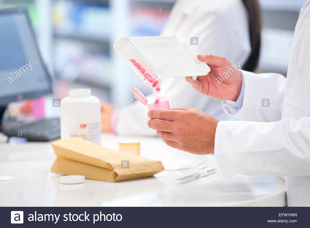 Close up of pharmacists hands counting and dispensing medication - Stock Image