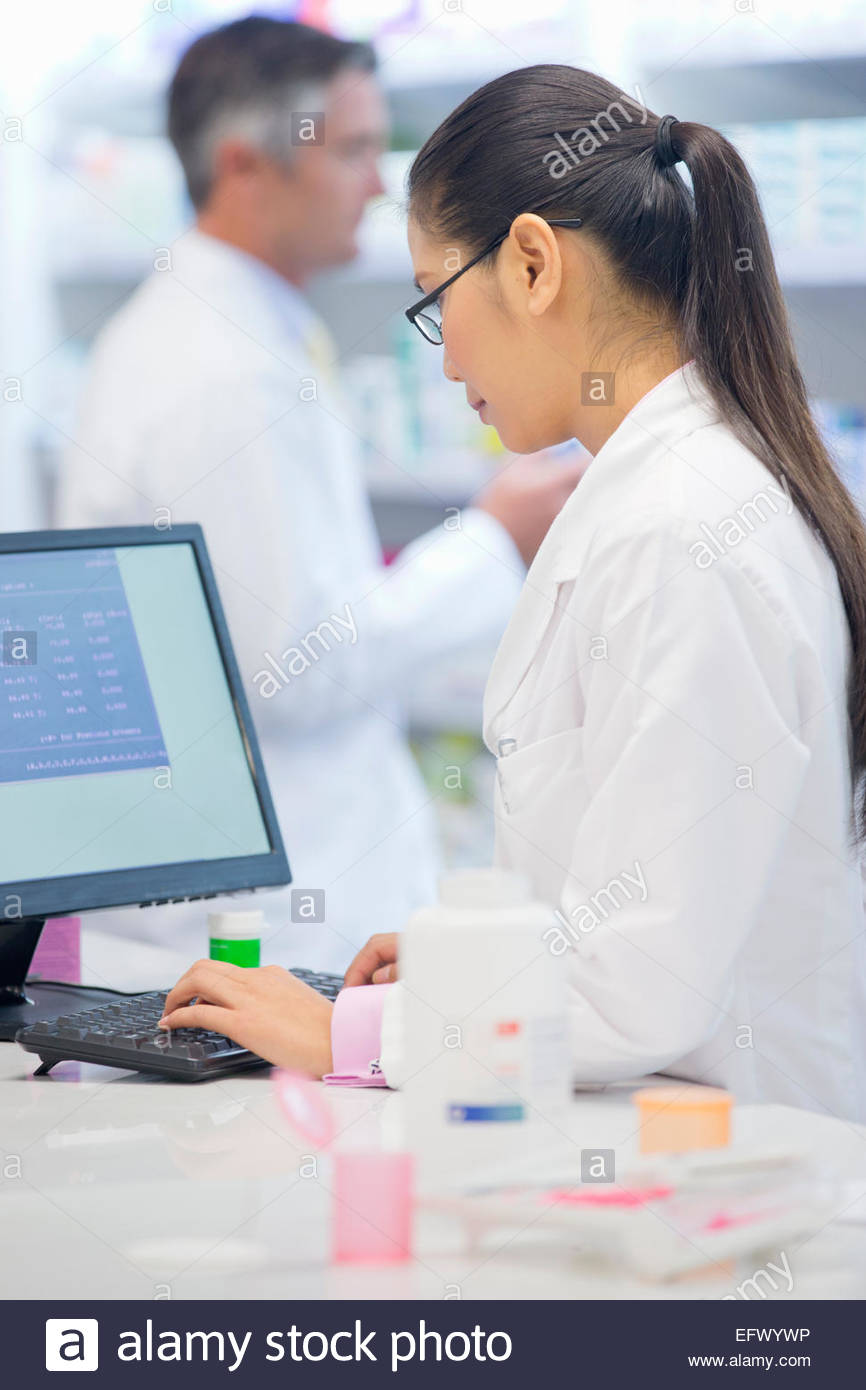 Pharmacist working on computer behind pharmacy counter - Stock Image