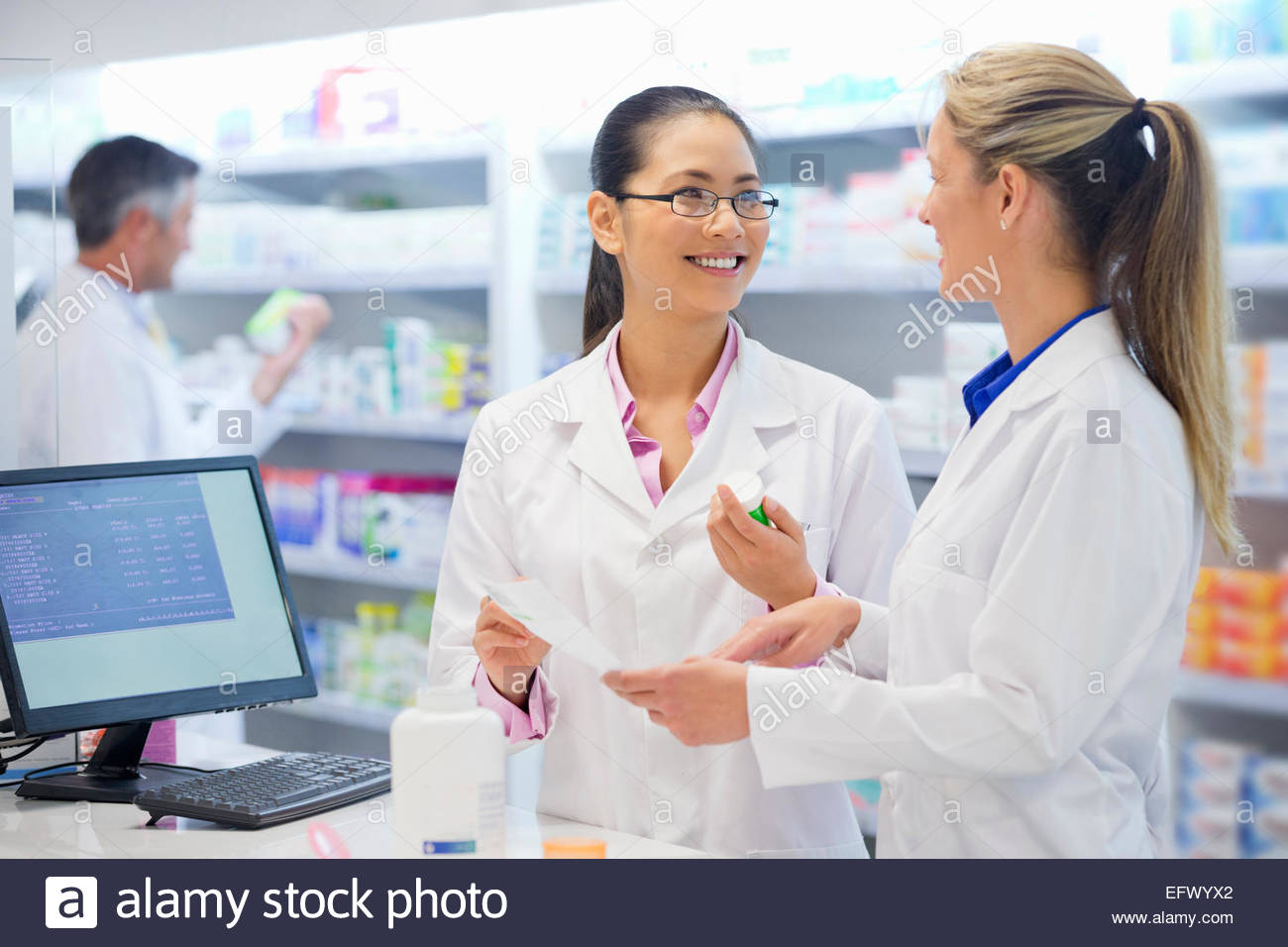 Pharmacist, holding prescription, smiling and talking to colleague in pharmacy - Stock Image