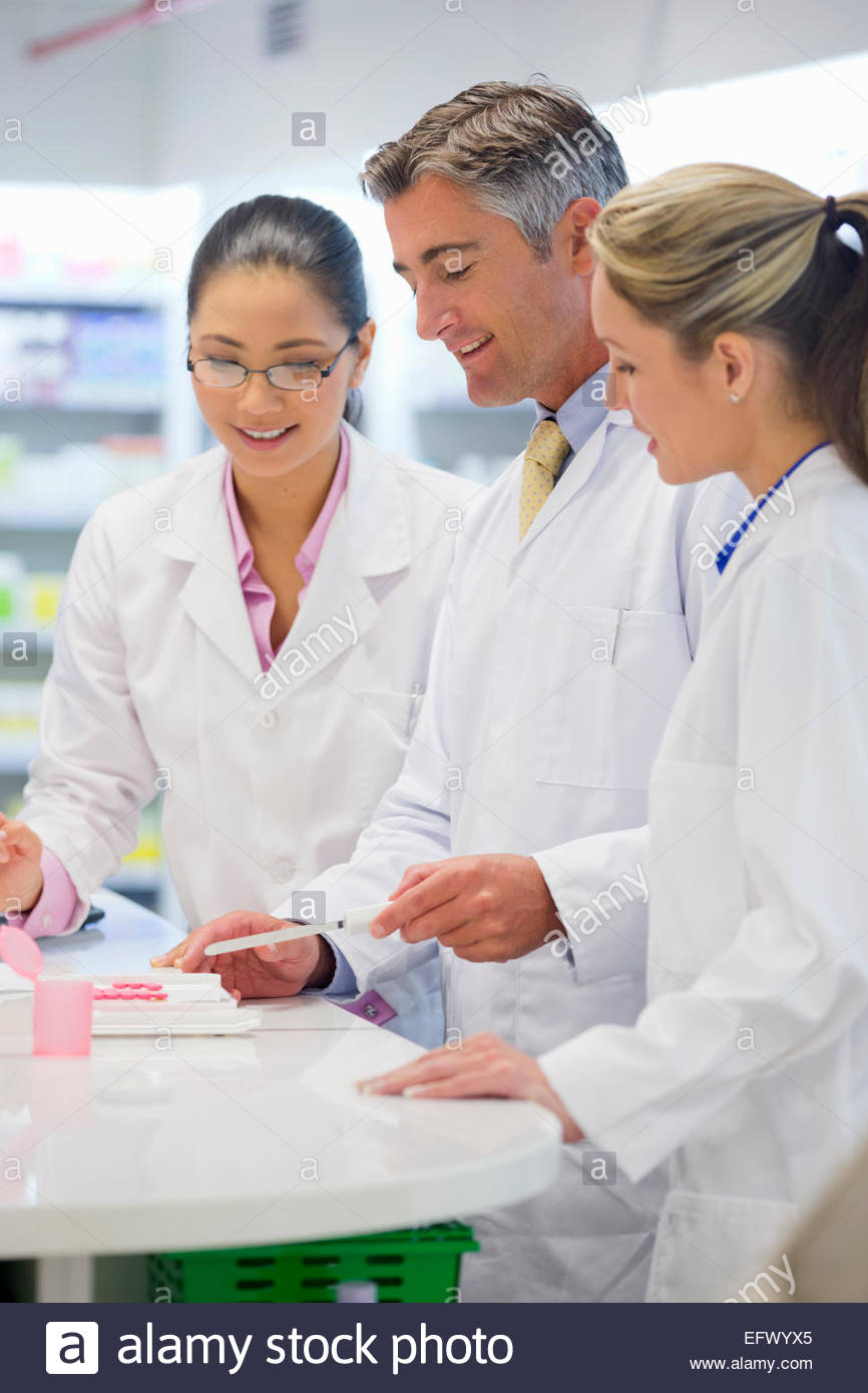 Pharmacist, counting medication, smiling and talking to colleagues in pharmacy - Stock Image