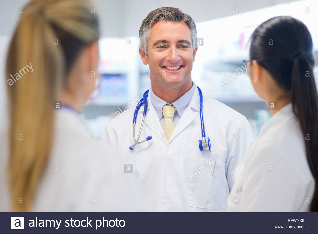 Doctor, wearing stethoscope, smiling at colleagues - Stock Image
