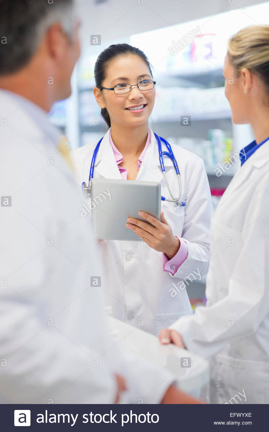 Doctor, wearing stethoscope, with digital tablet, talking to colleagues - Stock Image