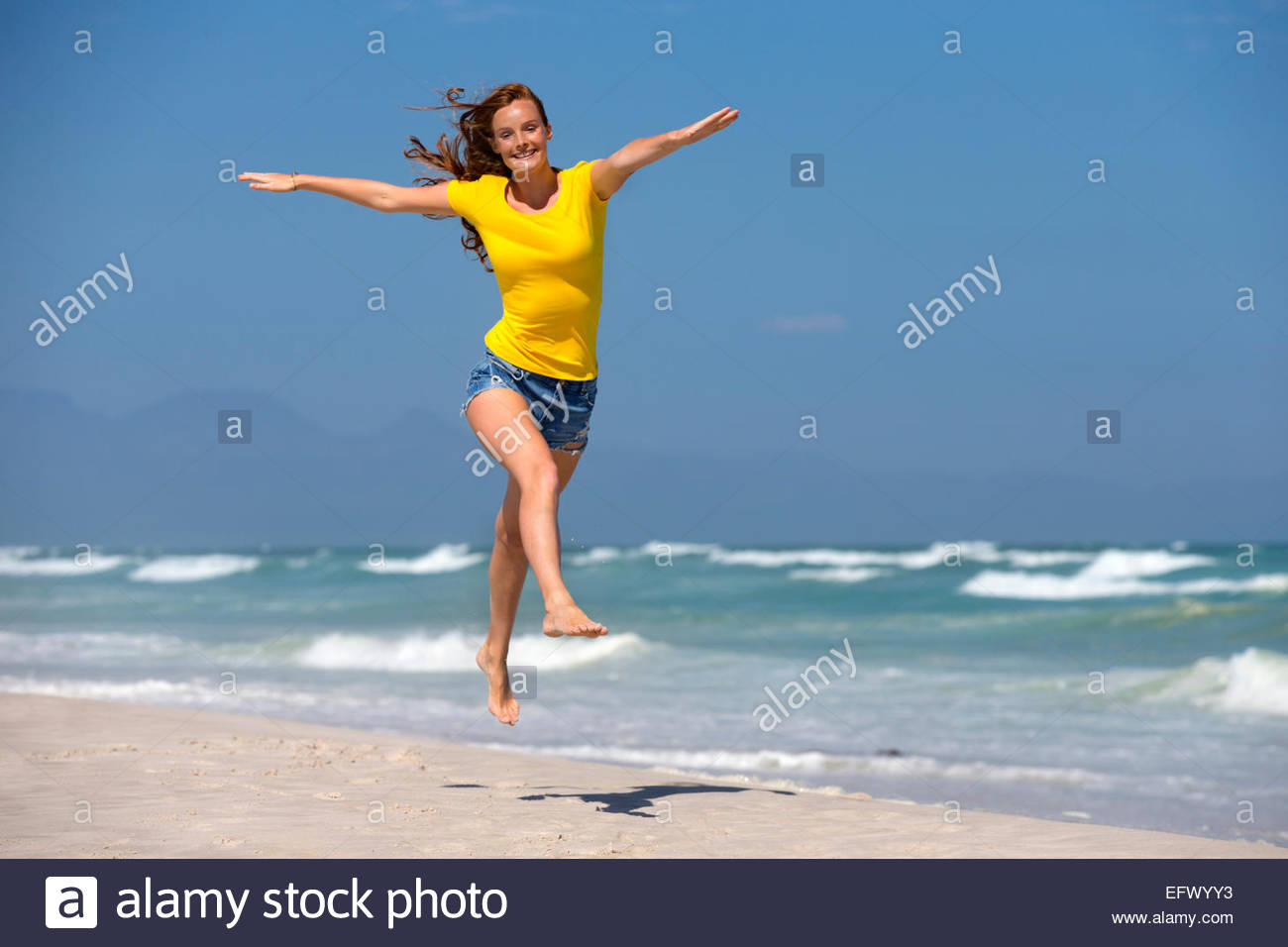 Happy woman, with arms outstretched, leaping in air on sunny beach - Stock Image