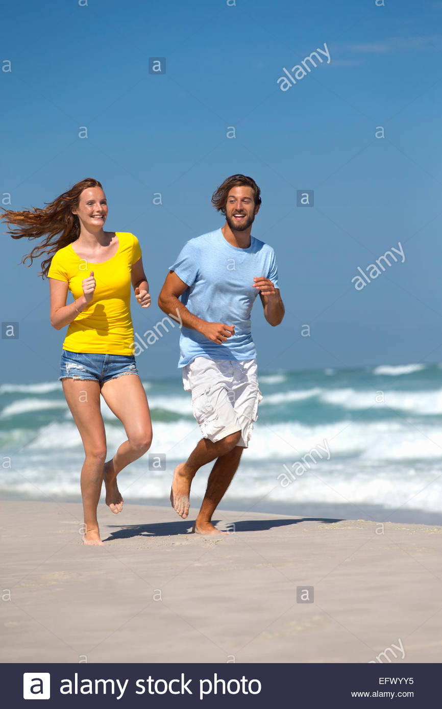 Happy couple, smiling and running on sunny beach - Stock Image
